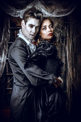 Beautiful man and woman vampires dressed in medieval clothing stand in a room of the old abandoned castle. Halloween.