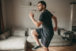 beautiful man doing exercises, running in room. Sport in quarantine at home, isolation, covid, virus.