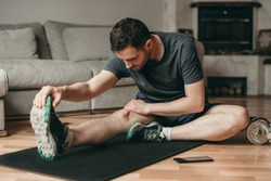 beautiful man doing stretching exercises on a mat. Sport in quarantine at home. Online lessons. Workout with an application on a smartphone.