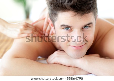 Beautiful man enjoying a back massage in a Spa center