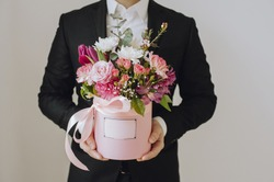 Beautiful man in a suit holding hands festive pink box with delicate flowers. The box can insert your logo and text. Gift to Women's Day. Agency floral design. Gift bouquet on March 8