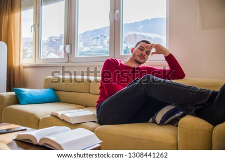 Beautiful man is sitting on the sofa and learning from scripts #1308441262