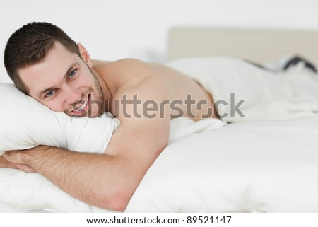 Beautiful man lying on his belly in his bedroom