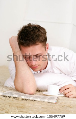 Beautiful man lying on the mat with the paper on a light background