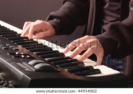 Beautiful man's hands on the keys of synthesizer