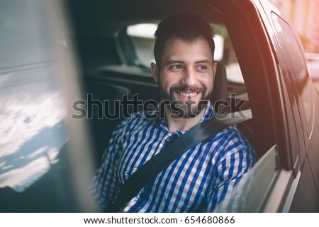 Beautiful man smiling while sitting on back seat in the car