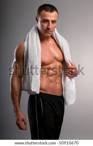 Beautiful man with muscular body holding the towel.