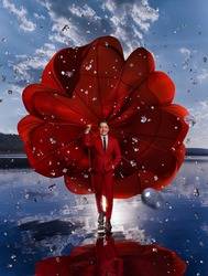 Beautiful man with red parachute above the lake