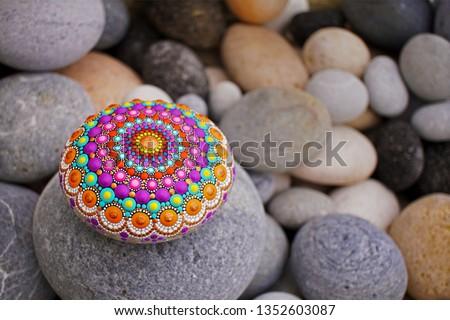Beautiful mandala hand painted on a sea stone, with pebbles