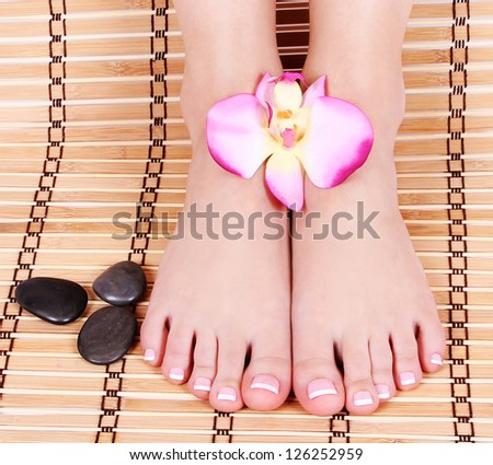 beautiful manicured female bare feet with orchid flowers and spa stones over bamboo mat, pedicure, foot care feet care, spa