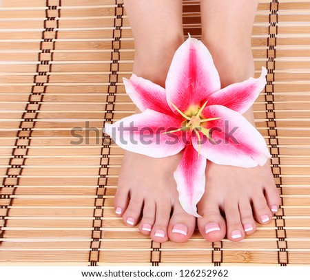beautiful manicured female bare feet with pink lily flower over bamboo mat feet care,  spa