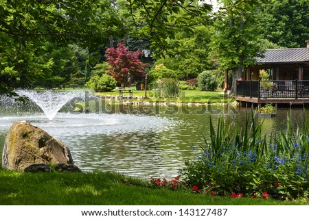 Beautiful Manicured Garden With A Deck Overlooking A Pond With A Fountain That\'S Surrounded With Potted Plants And Flower Beds.