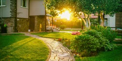 Beautiful manicured lawn and flowerbed with deciduous shrubs on private plot and track to house against backlit bright warm sunset evening light on background. Soft focusing in foreground.
