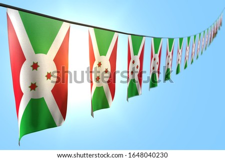 beautiful many Burundi flags or banners hangs diagonal on string on blue sky background with selective focus - any feast flag 3d illustration