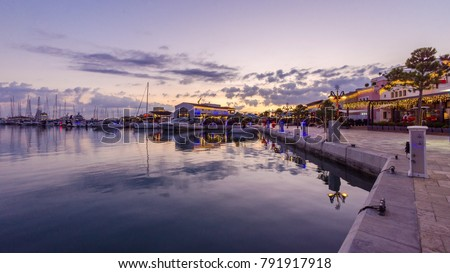 Beautiful Marina,Limassol city Cyprus at dusk. Modern, high end life, newly developed port, docked yachts, restaurants, shops, a landmark for waterfront promenade.View of the commercial area at sunset #791917918