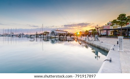 Beautiful Marina, Limassol city Cyprus. Modern, high end life in newly developed port with docked yachts, restaurants, shops, a landmark for waterfront promenade. View of the commercial area at sunset #791917897