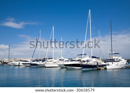 Beautiful marina view, sailboats and motorboats in blue water