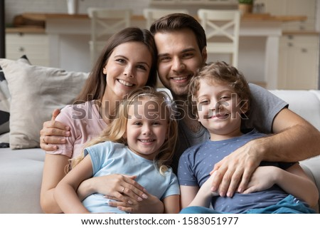 Beautiful married couple and little pre-school children pretty son and sweet daughter sitting on couch looking at camera feels happy. Concept of welfare full family portrait, new home, capture moment