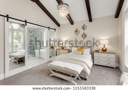 Beautiful Master Bedroom in New Luxury Home with View of Ensuite Bathroom. Features Wood Beams on Ceiling and Sliding Barn Door