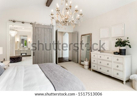 Beautiful master bedroom in new luxury home with view of ensuite master bathroom. Features barn door, chandelier, and elegant furnishings.  Сток-фото ©