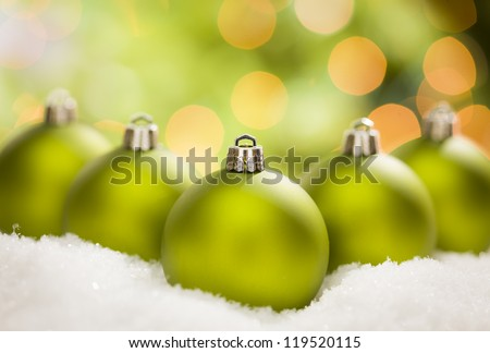 Beautiful Matt Green Christmas Ornaments on Snow Flakes Over an Abstract Background with Room For Your Own Text. - stock photo