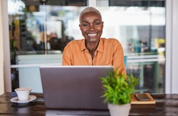 Beautiful mature african woman sitting in a bar outdoor and working with laptop - Black woman looking in camera and smiling