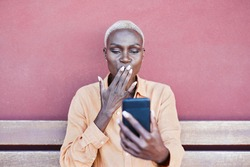 Beautiful mature african woman sitting outdoor while sending kisses with hand on a video call - Elderly trendy person enjoy technology