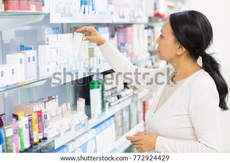 Beautiful mature Asian woman choosing cosmetics at the drugstore reaching for something on a shelf copyspace pharmacy buyer shopping shop store consumer customer purchase beauty lifestyle
