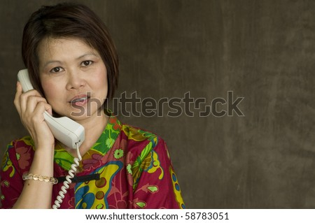 Beautiful mature Asian woman with telephone