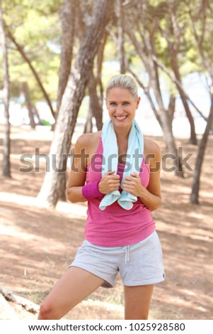 Beautiful mature blond woman recovering from exercising in park with towel around neck, looking smiling in sunny outdoors. Healthy well being fitness, active sport leisure, body training lifestyle.