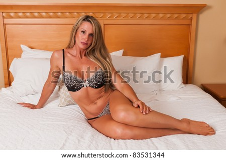 Beautiful mature blonde in bed in brown lingerie - stock photo