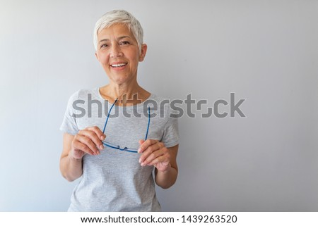 Beautiful mature business woman isolated over grey background. Attractive middle aged woman with beautiful smile. Portrait of mature business woman smile while standing against grey background.