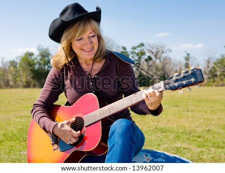 Beautiful mature country western woman strumming her guitar and singing.
