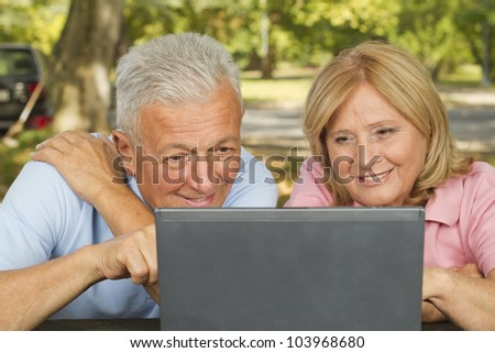 Beautiful mature couple enjoy using laptop in park