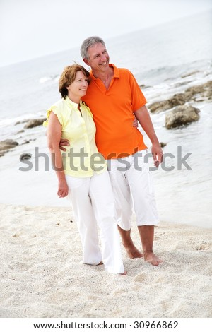 stock photo beautiful mature couple walking along the beach 30966862 Happy mature couple using