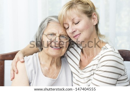 Beautiful mature daughter with closed eyes hugging her senior mother.