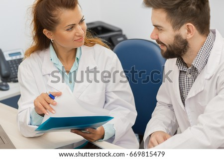 Beautiful mature female doctor discussing medical survey results with her male colleague at the clinic people communication team teamwork professionalism profession occupation career job talking