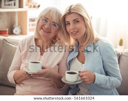 Beautiful mature mother and her adult daughter are drinking coffee, looking at camera and smiling while sitting on couch at home #561661024