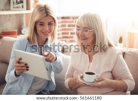 Beautiful mature mother and her adult daughter are drinking coffee, using a digital tablet and smiling while sitting on couch at home #561661180