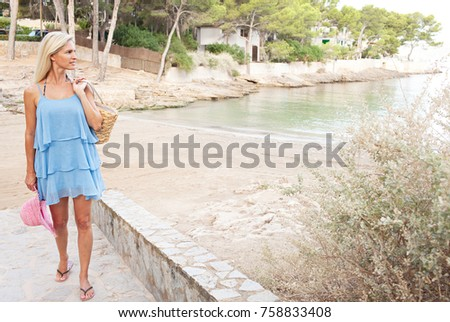 Beautiful mature tourist woman arriving at beach on holiday nature exterior. Healthy wellness lifestyle, travel recreation. Female walking on beach path carrying basket bag, relaxing destination.