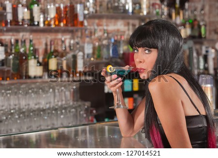 Beautiful mature white female holding martini and looking over