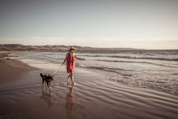 Beautiful mature woman and pet dog off leash walking along the sea shore on remote empty beach. Companionship Benefits of animals Keeping active Retirement lifestyle and Dog friendly tourism.