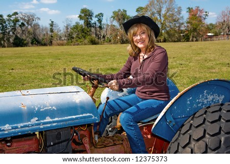 stock photo : Beautiful mature woman driving a tractor on her farm.