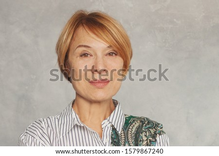 Beautiful mature woman face on gray background