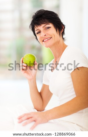 beautiful mature woman holding a fresh green apple