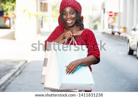 beautiful mature woman in loincloth standing outdoors holding shopping bags and looking at camera smiling smiling. #1411831238