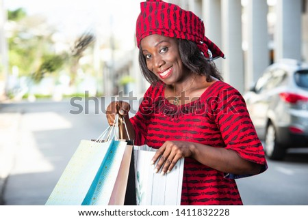beautiful mature woman in loincloth standing outdoors holding shopping bags and looking at camera smiling smiling. #1411832228