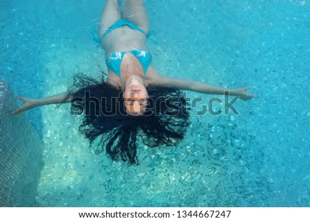 beautiful mature woman in prime age with dark curly hair in blue bikini in sunlight floats elegantly floating happily floating in turquoise blue water in the spa pool #1344667247