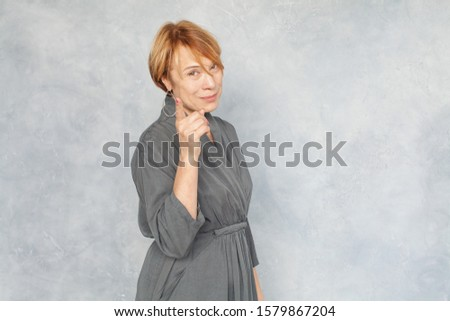 Beautiful mature woman pointing finger on gray background