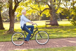 beautiful mature woman riding a bike at the park